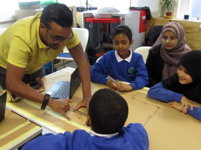 Salesforce volunteer programmes robots with pupils at FabLab
