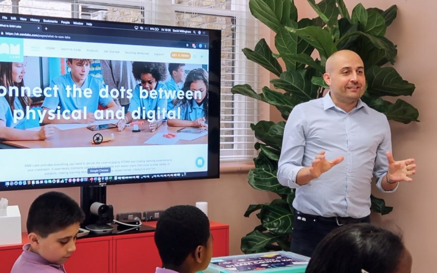 Man presenting to children about jobs in tech, the screen reads Connecting the dots between physical and digital